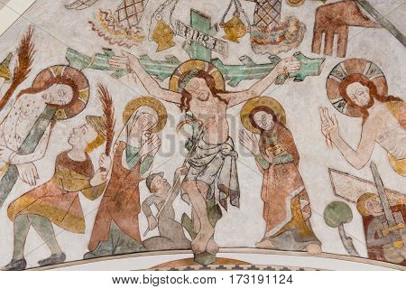 The crucifixion of Jesus on Good Friday. His mother Mary and St. John standing at the cross with the heading INRI. Gothic fresco in Skibby church Denmark - February 21 2017
