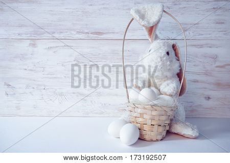 easter bunny with basket and eggs on white wooden background
