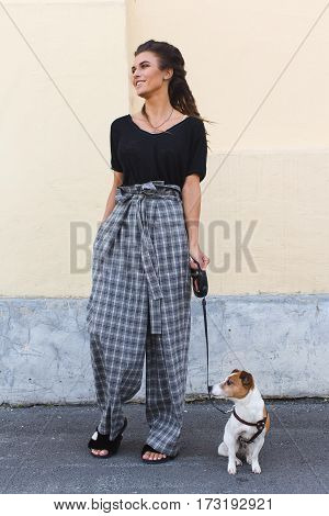 Pretty young female in checked stylish clothes dress in a cage walking a dog. Vertical outdoors shot.