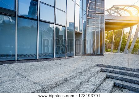 exterior of glass office building with stone steps.