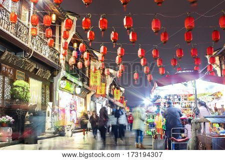 Chinese tourist street at night with red lanterns. People on the move at slow shutter speeds.
