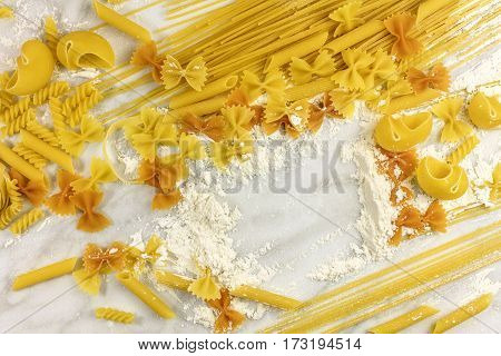 Various types of pasta on a white marble table with flour, forming a frame for text
