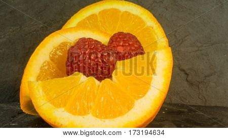 Raspberries and oranges on a background of slate