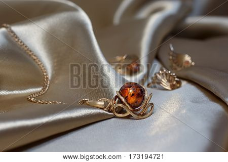 Closeup gold chain with pendant from gold and authentic baltic amber on light brown atlas. Gold earrings and ring with amber on background. small DoF focus put only pendant