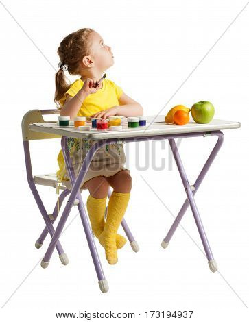 Cute three-year girl is painting with paintbrush and colorful paints. Adorable baby girl drawing, sitting behind table with fresh fruits and looking upward and right, isolated on white background.