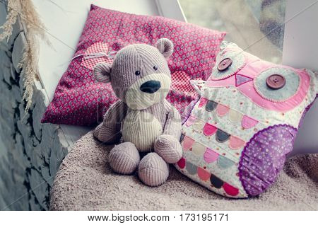 Provence style interior - warm and cozy window seat with Teddy Bear and cushions. Light home decoration in pink and purple tones. Retro living room.