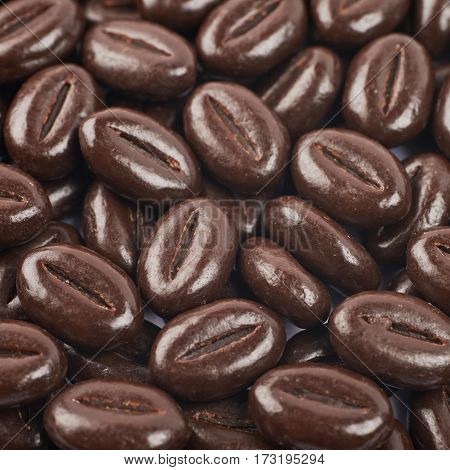 Surface coated with coffee bean shaped chocolate candies as a close-up backdrop composition