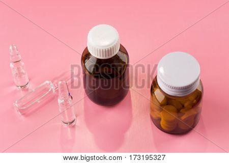 Pills bottles and medicine ampule on color background