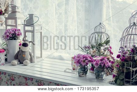 Provence style interior-beautiful pink and purple bouquets in vase and cages over window. Light home decoration with flowers asters chrysanthemums. Retro living room. Vintage holiday floral concept.