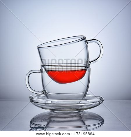 Two cups of clear glass of tea facing each other with saucers.