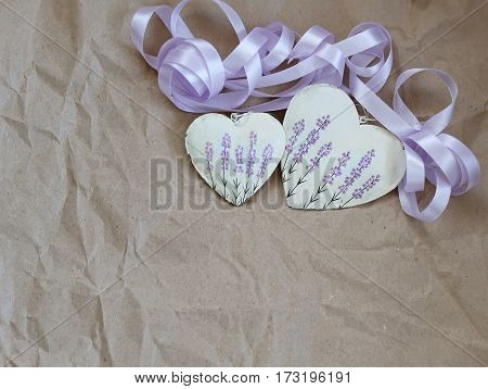 two hearts with lavender picture and purple ribbon on the background of old paper. Soft focus background mode.