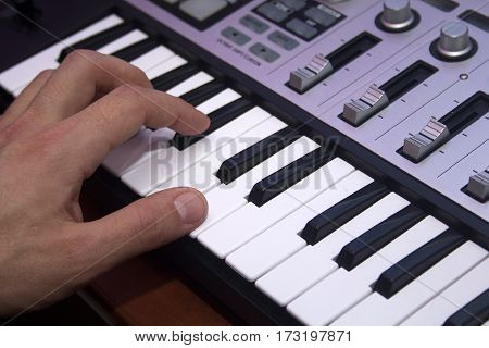 young man playing on a MIDI keyboard