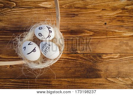 Eggs with painted smiling faces in a basket on wooden bacground