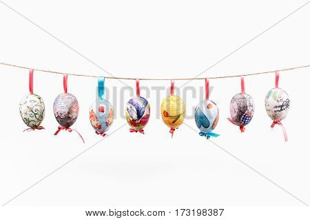 Pretty Colored Easter Eggs hanging on wire isolated on white