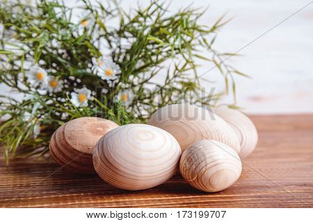 wooden eggs with green grass preparing for easter on wooden background