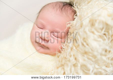 Sweet hairy baby sleeping on a furry yellow pillow, wrapped up with a blanket, closeup