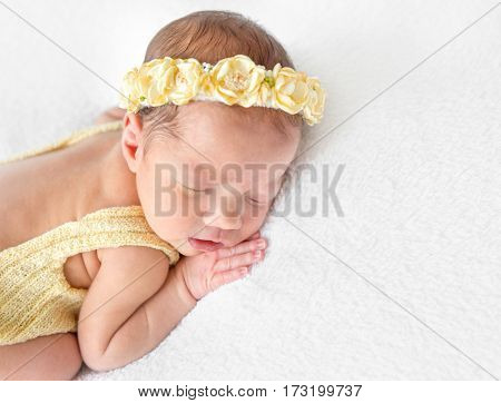 Amazing little kid in a yellow knitted costume napping on her tummy, closeup