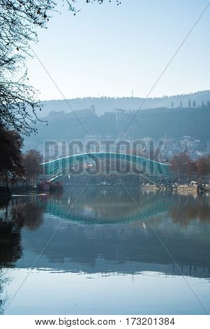 TBILISI GEORGIA - JANUARY 5 2017: A view to an old town of Tbilisi Peace bridge and mountains around the city from Kura's embankment early in the morning Georgia Caucasus mountains.