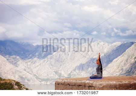 Woman Practicing Yoga In Mountains