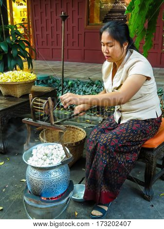 BANGKOK, THAILAND - JANUARY 17, 2014: Unidentified girl unwinds silk thread from silkworm cocoons in the boiling water. Motion blur. The Jim Thompson House, Bangkok, Thailand