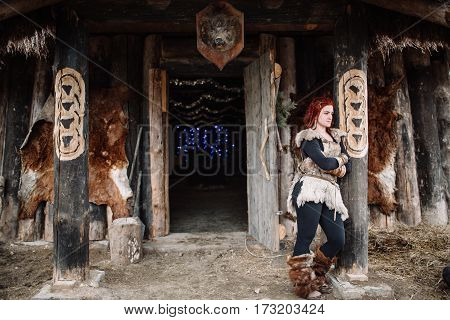 red-haired Viking in uniform leaning on a pillar