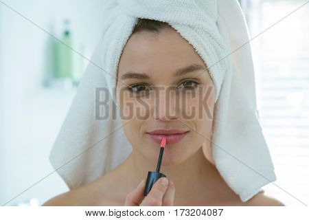 Portrait of woman applying lip gloss on her lips in bathroom at home