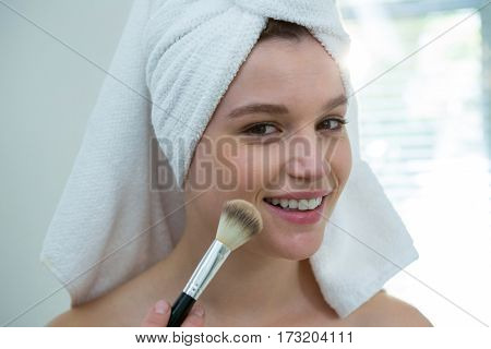 Portrait of woman applying make-up on her face in bathroom at home