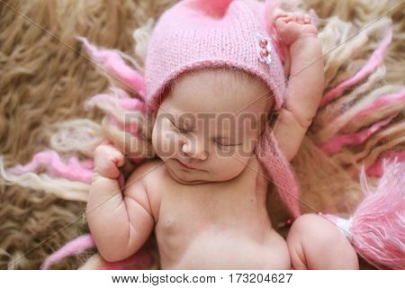 tender newborn baby in a pink cap sleeps stretching on a gentle background of wool