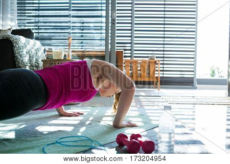 Woman doing exercise in living room at home