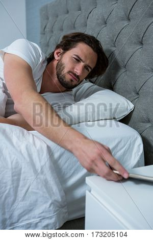 Man waking up with mobile alarm clock in bedroom at home