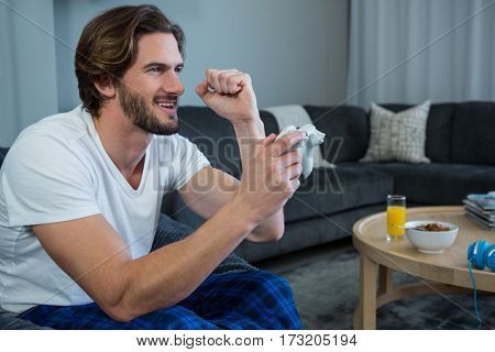 Man playing video games in living room at home