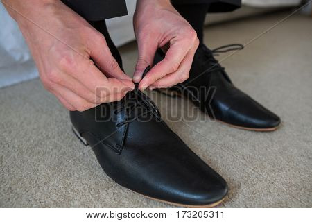 Man tying a shoelaces in bedroom at home