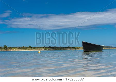 Blue dinghy water level point of view afloat on peaceful calm estuary Ngunguru Northland New Zealand