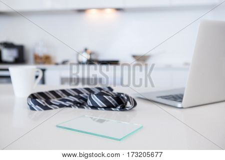 Tie with coffee mug and laptop in kitchen at home