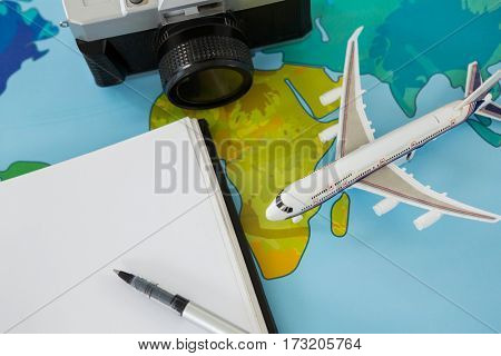 Close-up of digital camera, dairy, pen and airplane model on table