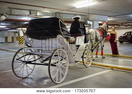 Woman stands near horse, coach and coachman in underground parking