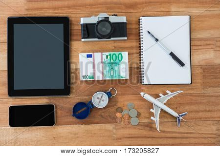 Electronic gadgets, camera, dollar, coin, diary, pen, compass, and airplane model on table
