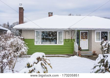 Family house with front yard in snow. Colorful residential house on winter cloudy day