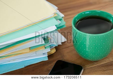 Close-up of coffee mug, mobile phone and stacked files on table