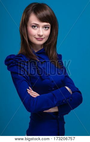 Businesswoman isolated on blue background. Young smiling caucasian business woman standing looking at camera.