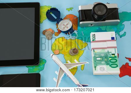Electronic gadgets, camera, dollar, compass, and airplane model on table