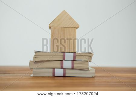 Model house on a pile of money against white background