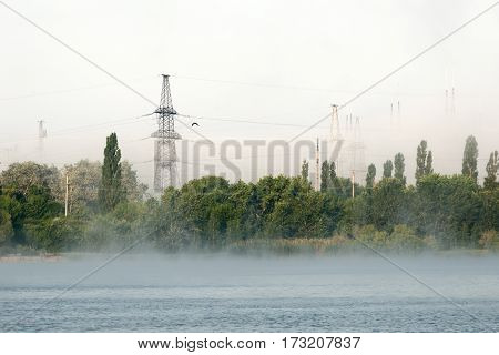 Foggy morning on the lake. Beyond the trees visible support high-voltage line.
