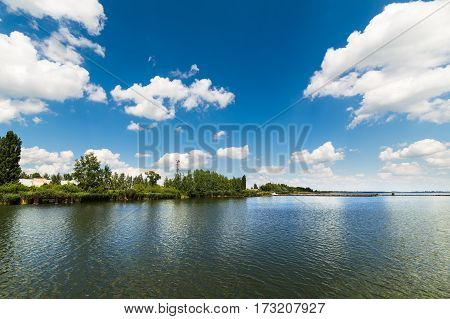 Big clean lake and white clouds in the blue sky. Sunny day.