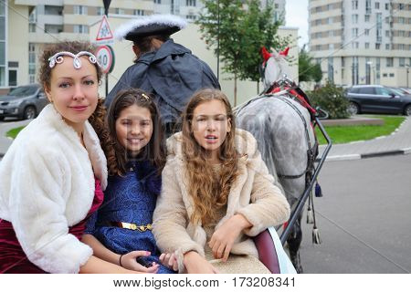 Two happy girls, woman sit in coach with coachman and horse near residential buildings