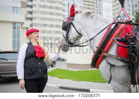 Pretty coachman woman stands with horse in red harness near residential buildings