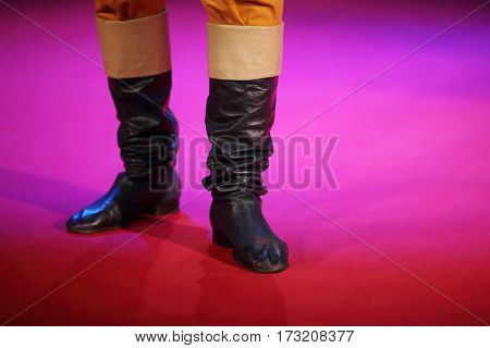 Theatrical sham soldier black leather boots on stage during performance