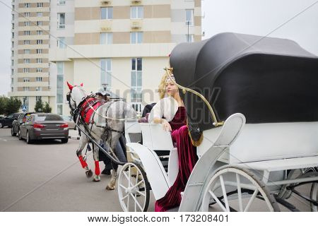 Pretty woman in long dress poses in coach with coachman near residential buildings