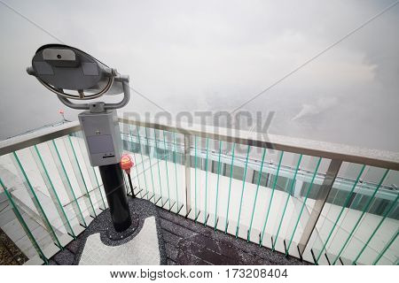 Binoculars on viewing platform on snowy day and buildings in fog in Moscow
