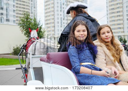 Two girls sit in coach with coachman and horse near residential buildings
